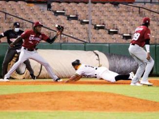 Wilmer Difó, de las Águilas, llega a la tercera base mientras que Oneil Cruz, de los Gigantes, trata de ponerlo out.