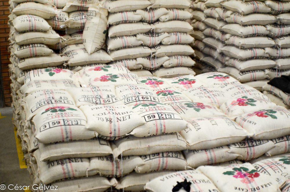 Amoncellement de sacs de café colombien, prêts à être exportés.