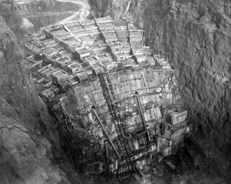 Hoover Dam takes shape from the concrete columns in which it was poured (shot from cableway control tower downstream on Nevada rim, so looking upstream)