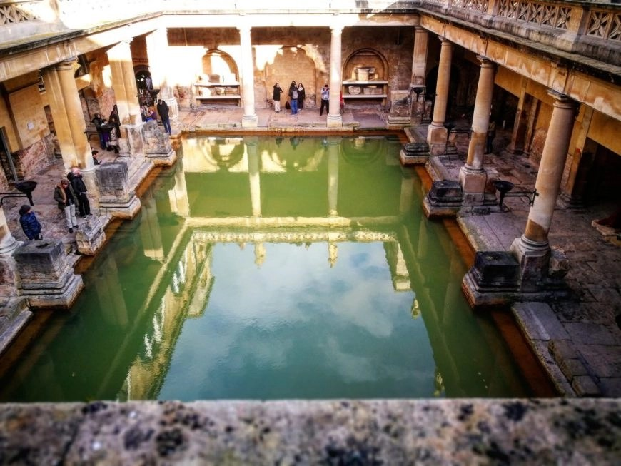 Destination Addict - Looking into the ancient hot springs at the Roman Baths in the city of Bath, Somerset.