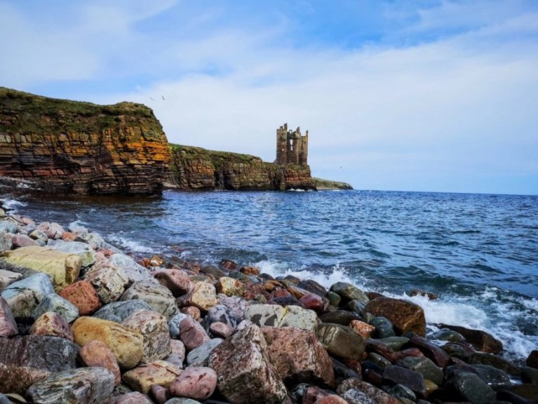 Looking up at Keiss Castle from Sinclair's Bay, NC500 – An Epic Itinerary For Scotland's North Coast - Destination Addict