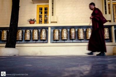 Monk walking by prayer wheel at Dalai Lama temple