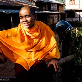 Young monk waiting for his ride