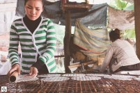 Young woman rolling rice paper to dry