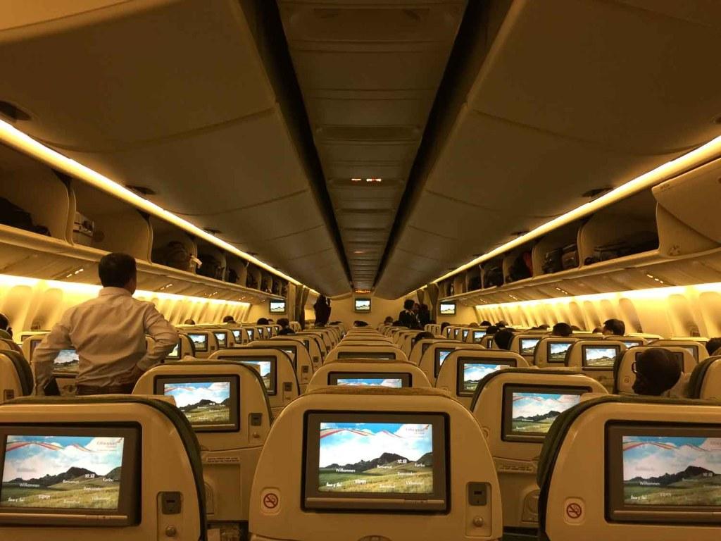 Poltronas do avião com monitores ligado