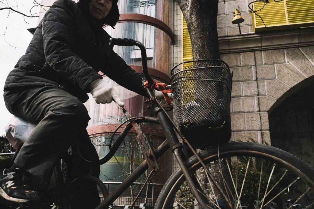 Chinês com bicicleta antiga no centro da cidade