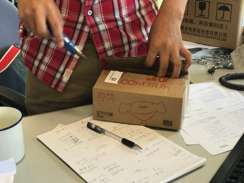 Compras online na China com JD Homem abrindo caixa de papelão com estilete