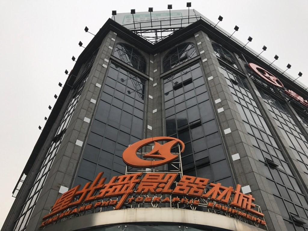 Mercado de câmera fotográfica antiga e nova em Xangai Fachada edifício vidros pretos e letreiro laranja