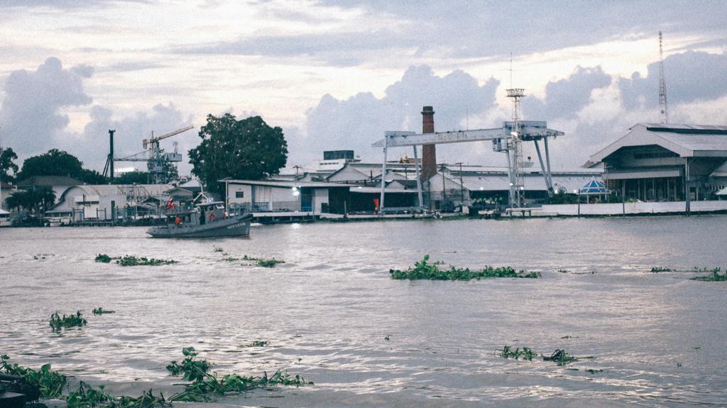 3 erros comuns durante a importação Imagem de barco navegando próximo à barracões industriais