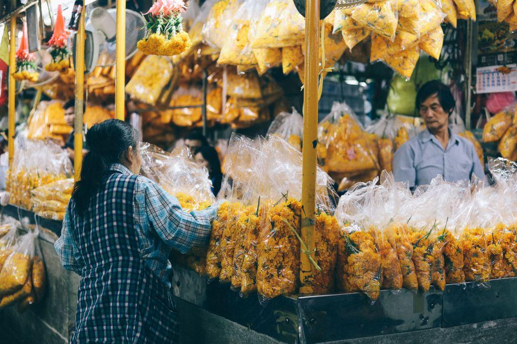 Qual o valor dos produtos, frete e seguro? Vendedora trabalhando no stand de flores em uma feira na China