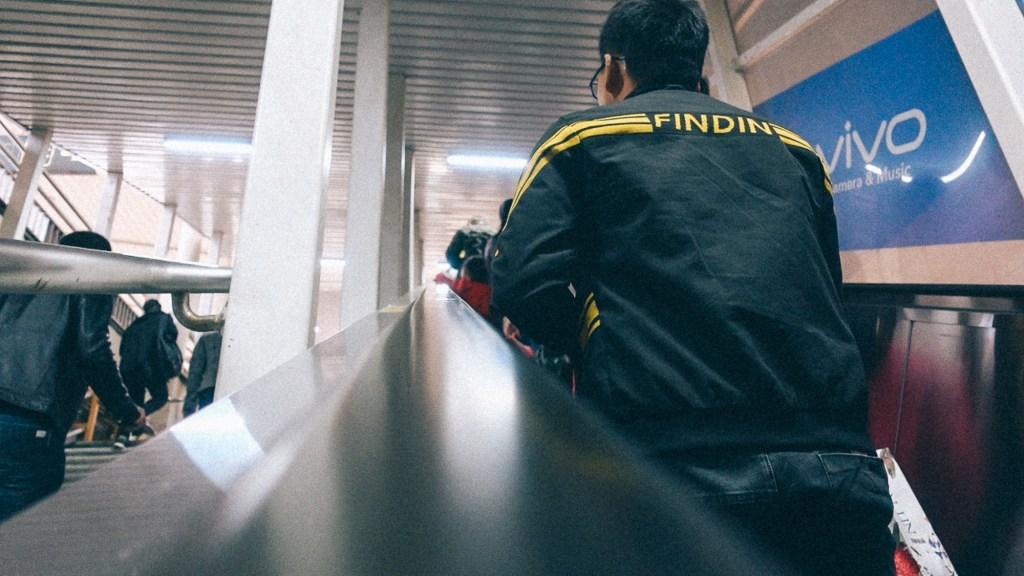 Como importar do vietnã Homem na escada rolante indo para a plataforma