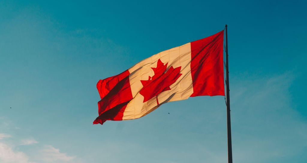 Viver no canada vale a pena Bandeira Canadá hasteada e céu azul