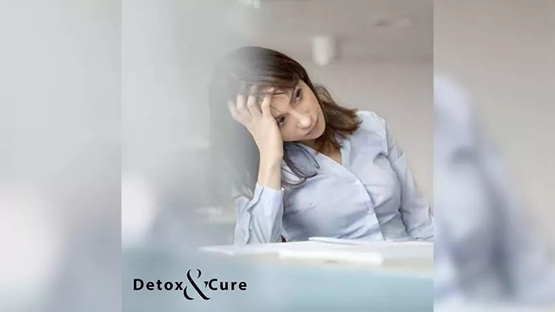 How do you Recover from Adrenal Fatigue - image of a woman in an office lookig fatigued as she is slumped to her left side holding her head in one hand. She is wearing a powder blue business shirt that buttons up and has a book on the desk in front of her as she look off into the distance