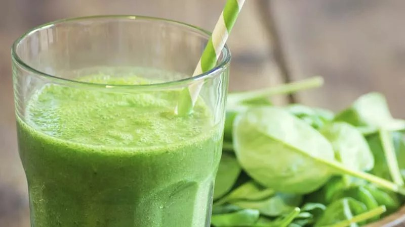 green juice in a glass on a timber table sitting next to a small pile of baby spinach leaves