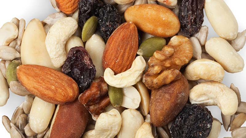 An Ancient Pulse Recipe that's Vegan and Keto Friendly - mixed dried fruit and nuts oncluding almonds, cashews, pepitas, brazil nuts, sunflower seeds, peanuts and currants on a white background
