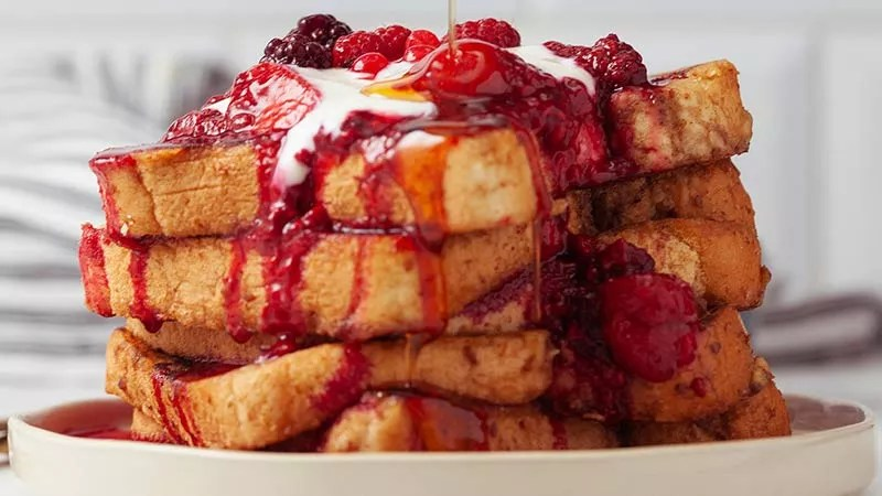 Delicious and Nutritious Sea Moss Vegan French Toast Recipe - Vegan French Toast stacked high on a round white plate topped with cherries and raspberries, Vegan cream, drizzled with Maple Syrup