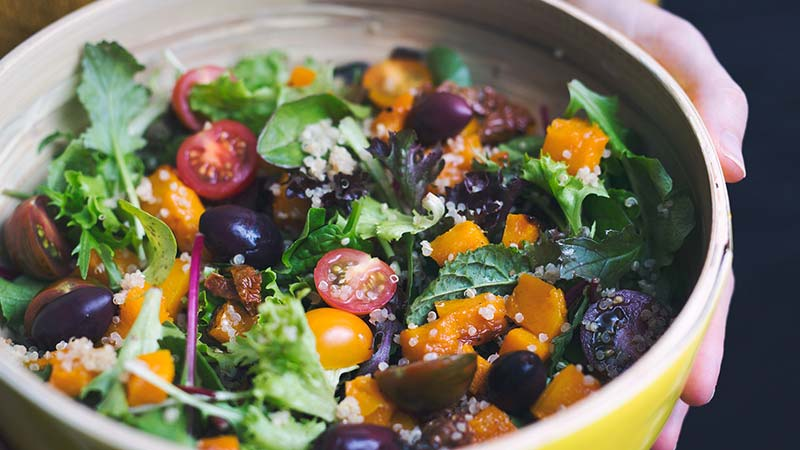 A Useful Vegan Intermittent Fasting Plan. Close up image of a beautiful plant based salad with cherry tomato, black olives, roasted pumpkin, finely sliced sundried tomato, mescalin salad, rocket and a topping of quinoa in a stoneware bowlbeing held by a young woman,