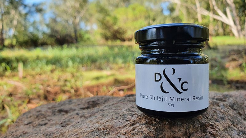 Shilajit Resin-Nature's Mineral Dense High Altitude Extract Featured Image with a photograph of a jar of Shilajit sitting on rock in Kakadu National Park with a lush green creek behind it