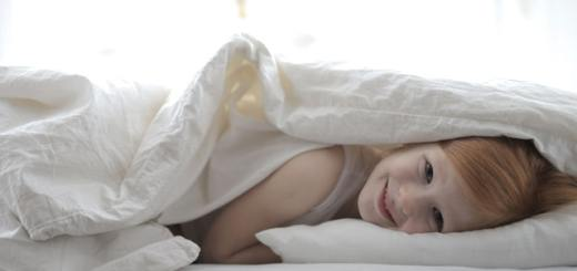 girl-lying-on-bed-covered-with-white-blanket