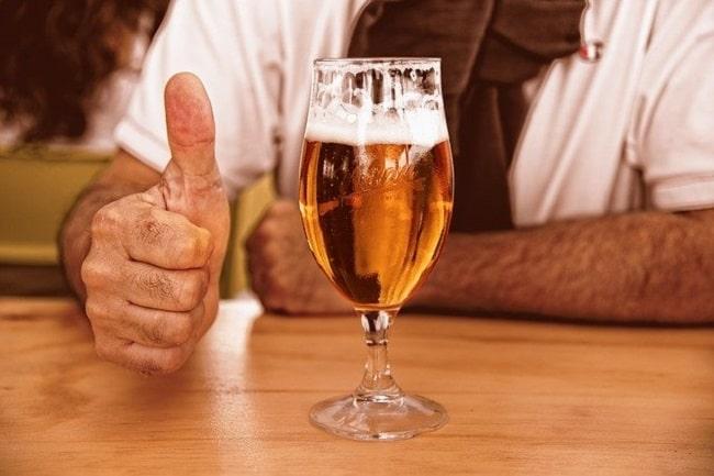 Un pouce levé à côté d'un verre de bière