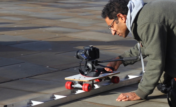 Behind the scenes of Two Feet Tall, director Andy Robinson has a camera on a skateboard type contraption running along rails - a dolly shot