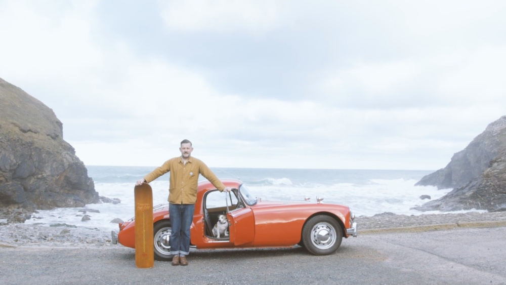 a man stands in front of a car in front of a beach. A still from Babies & Bellyboards, a documentary produced by Katherine Press