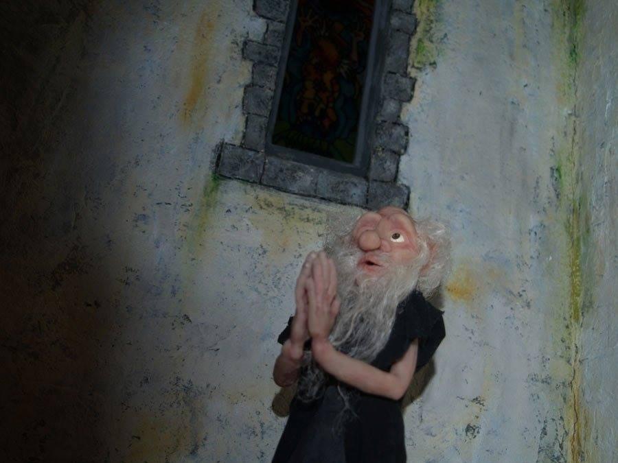 The Legend of Jan Tregeagle still: a puppet man with a long, grey beard prays under a window