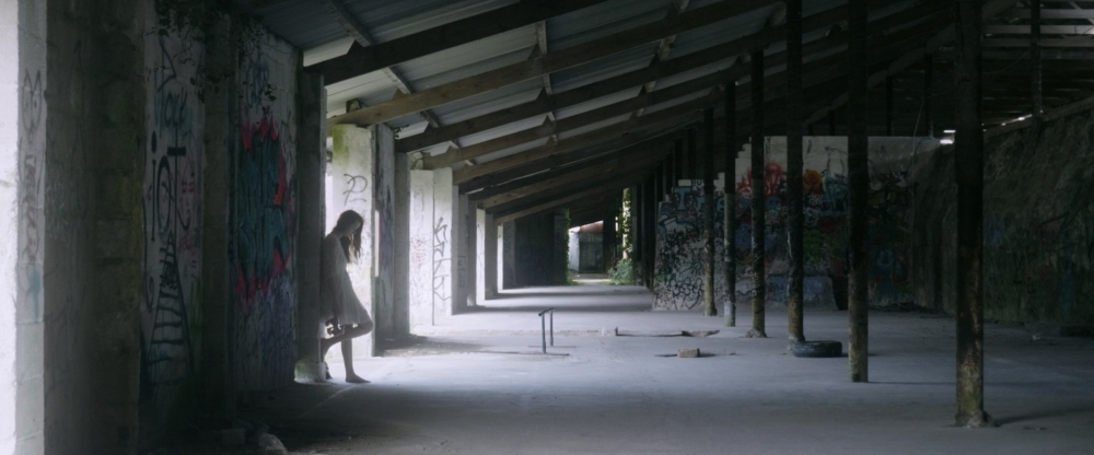 still from Billy Abbot's Elephant video for Haunt The Woods: in the half distance and half light a female figure stand with her back to the wall of a derelict building