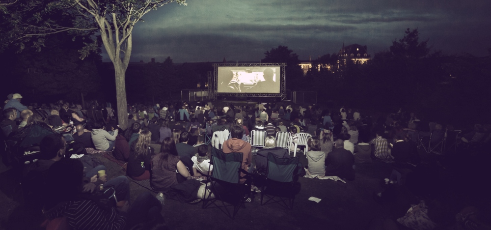 Exeter big screen in the park with people sitting in canvass chairs watching a film in the open