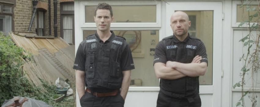 two men standing in police gear