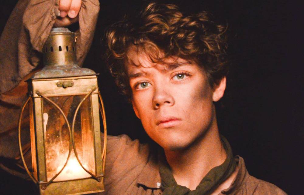 a boy from olden times with a dirty face is holding a lantern