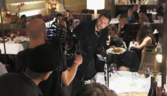 Steve Aaron-Sipple in the midst f a restaurant with cameras on him