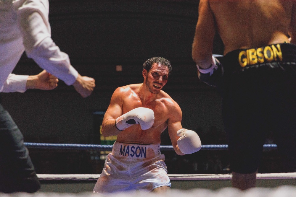 a man in white trunks is in a boxing ring he is looking tired and you see the back of his opponent and the referee