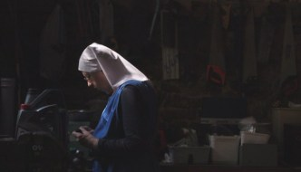 a nun in a white habit and a blue top is in a room