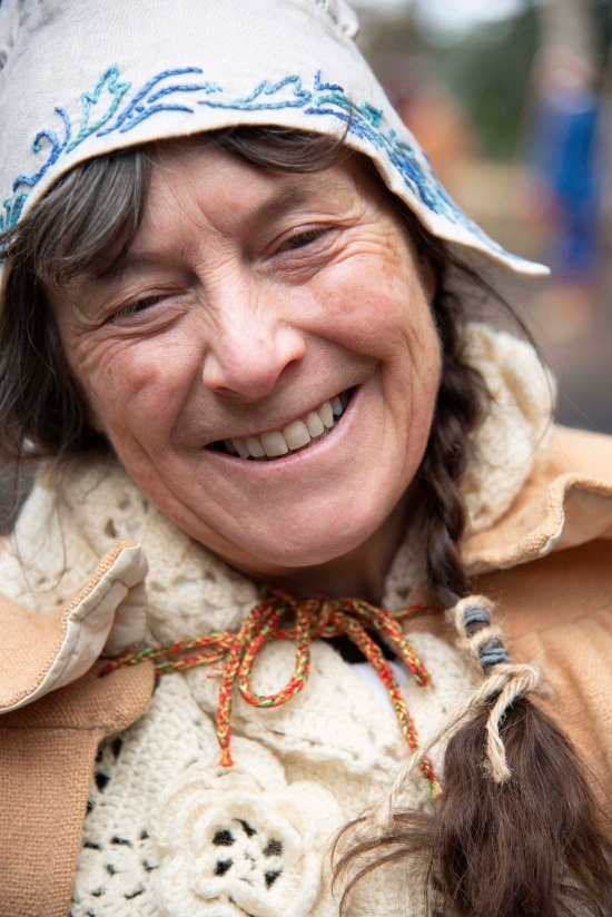 a close up of a woman's face as she wears old fashioned clothes