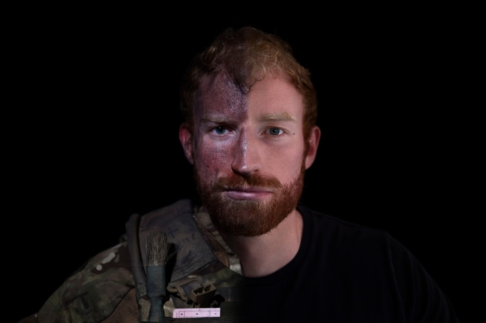 a man's face with a beard. Half of him is in army clothes with a dirty face, and half of him is clean and in civilian clothes