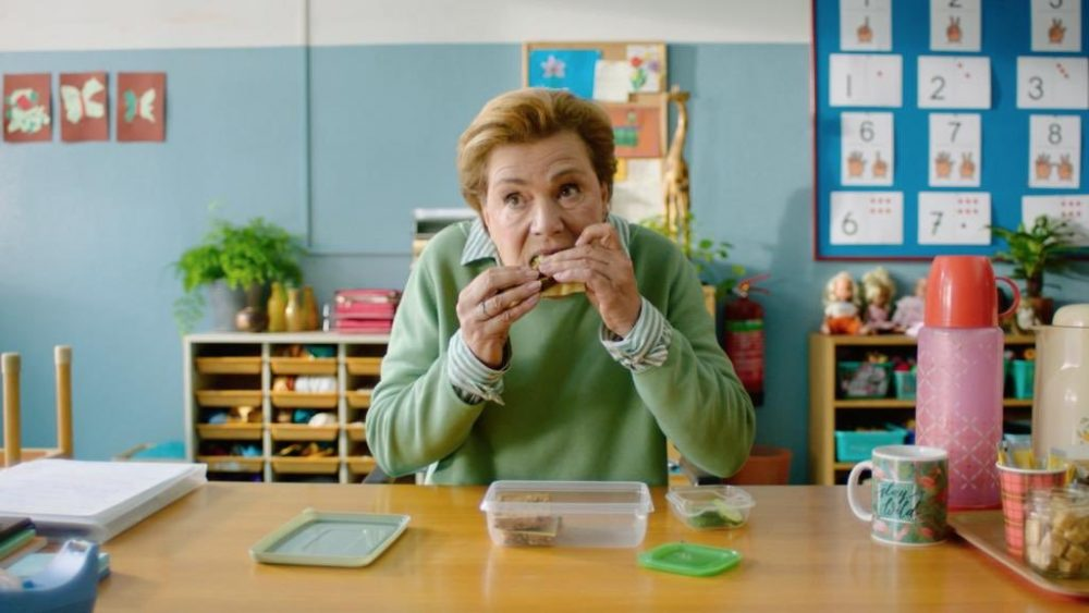 a still from the Jamille van Wijngaarden film school's out. An older woman is eating a sandwich from her packed lunch sitting at her desk in a primary school classroom