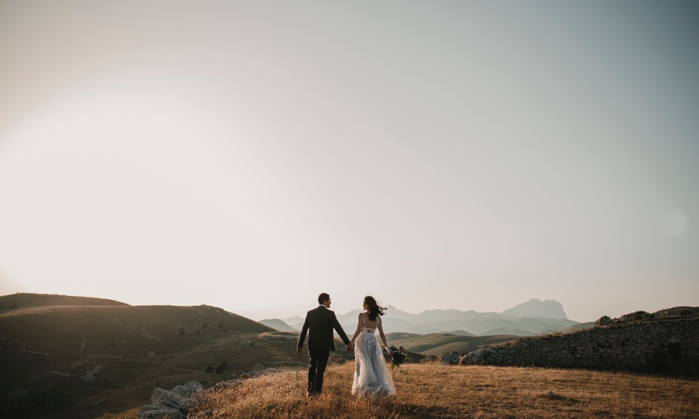 a male and female bride and groom on the top of hills