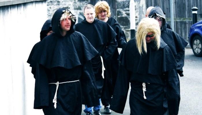 a group of men in black shawls walking down a street