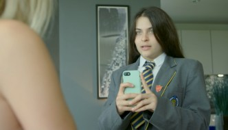 patrick still - a young girl in a school uniform is using her phone to take a picture of another girl - we only see the bare should of the other girl