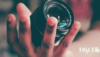 a person holding a dslr lense