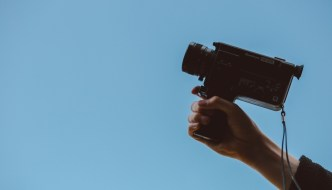 a person holding a video camera with a blue background