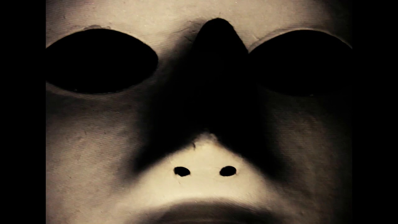 a plan white mask with no eyes and a black background