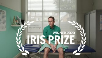 still from Short Calf Muscle - a man sitting on a bed, with the Irish Prize laurel on top