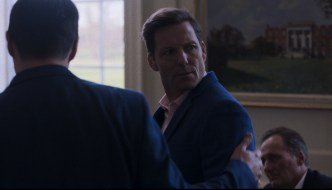 still from Avernus written by David Cunningham. A man is being escorted out of a room and is looking over his shoulder