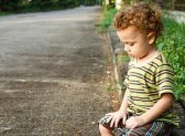 sad-little-boy-sitting-near-the-road