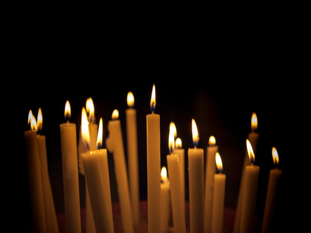 Close up of long candle sticks lit up in the dark, the candles are all white wax