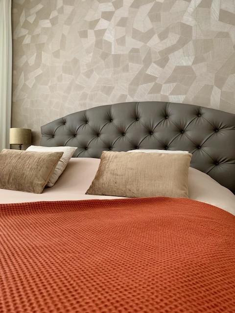 gecapitonneerd hoofdbord bed oranje sprei behang hotel chique