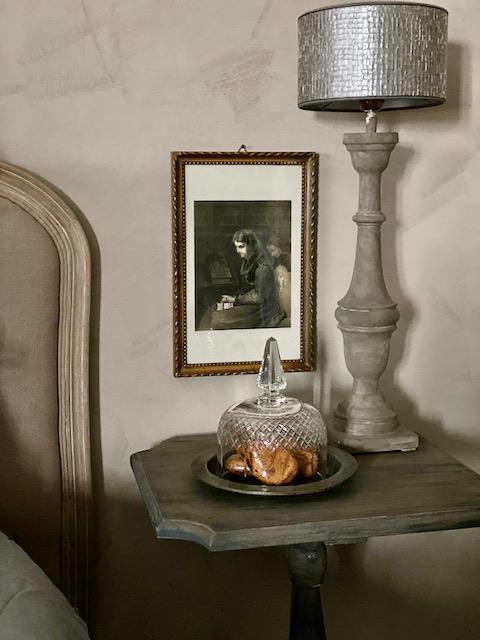 Klassiek hoofdbord bed wijntafeltje baluster schilderij naast bed