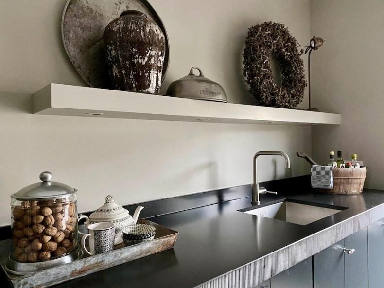 Landelijke zwarte keuken zonder bovenkastjes dienblad met theekan krans en zilveren cloche